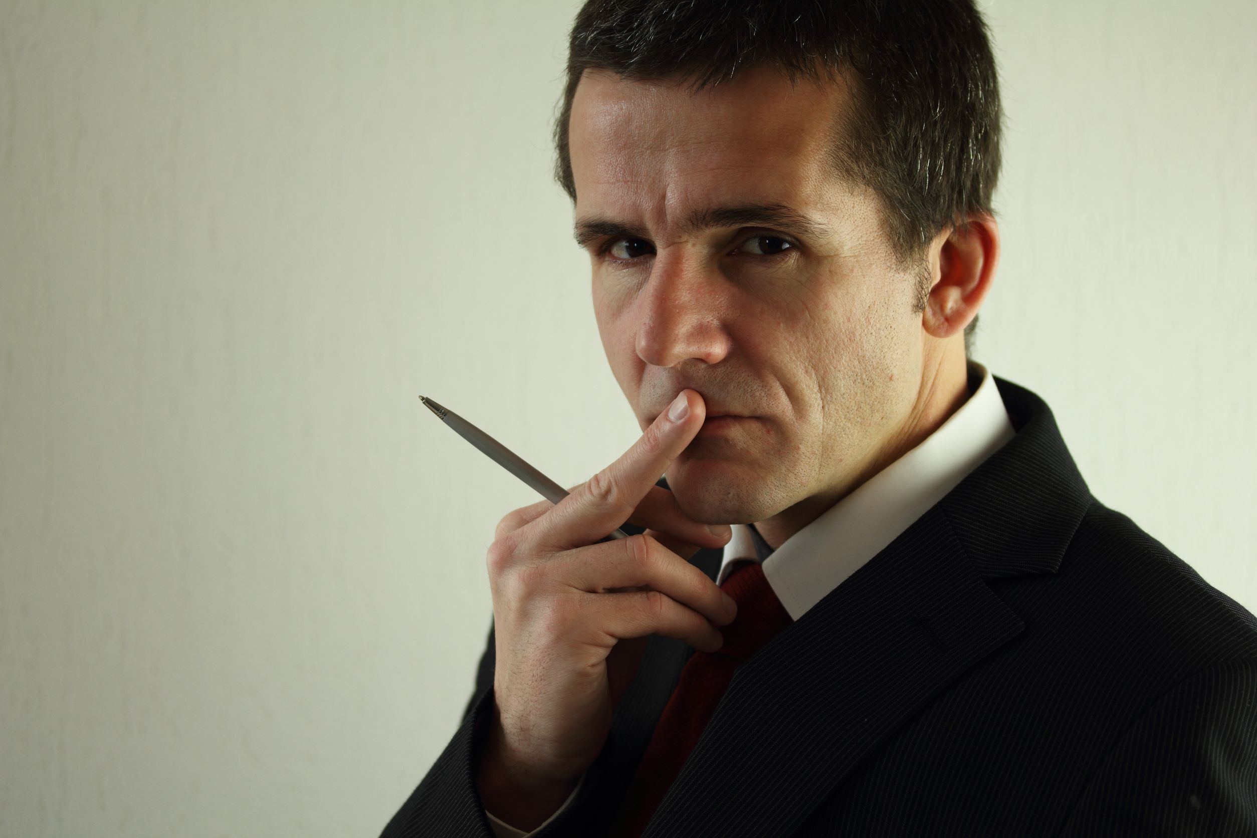 13790940 - a business man thinking over an idea he s in deep thought he s holding a pen